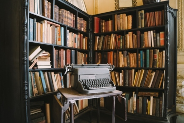 Interior of abandoned ornate Colonial Villa with books and typewriter